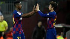 Riqui Puig y Ansu Fati chocan las manos durante un partido. (AFP)