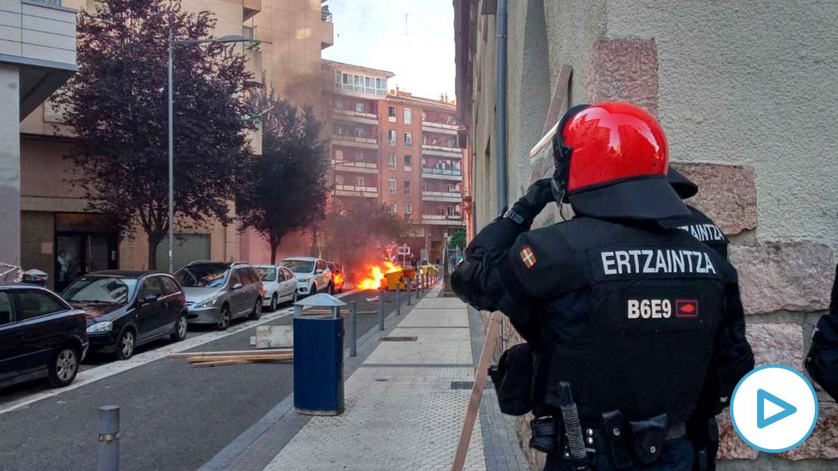 Un ertzaintza observa la quema de contenederos. Foto: Europa Press