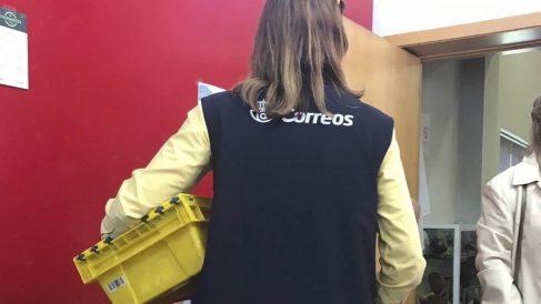 Una empleada de Correos recoge papeletas para el 12-J.
