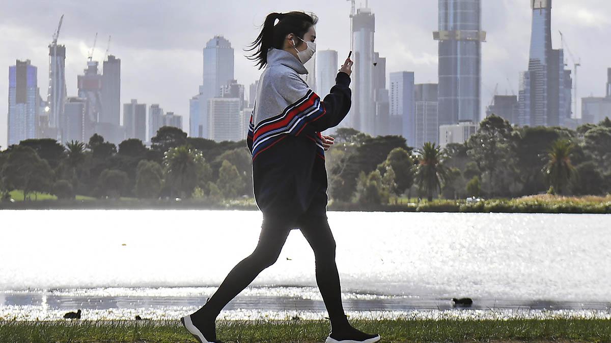 Una mujer hace ejercicio con Melbourne al fondo en plena psicosis por los rebrotes de coronavirus.