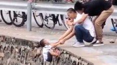 Padre sujeta a su hijo al borde del precipicio