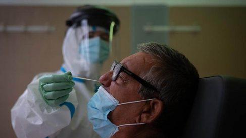 Una profesional sanitaria realiza una prueba PCR a un paciente en el CAP Raval Nord de Barcelona. (Efe)