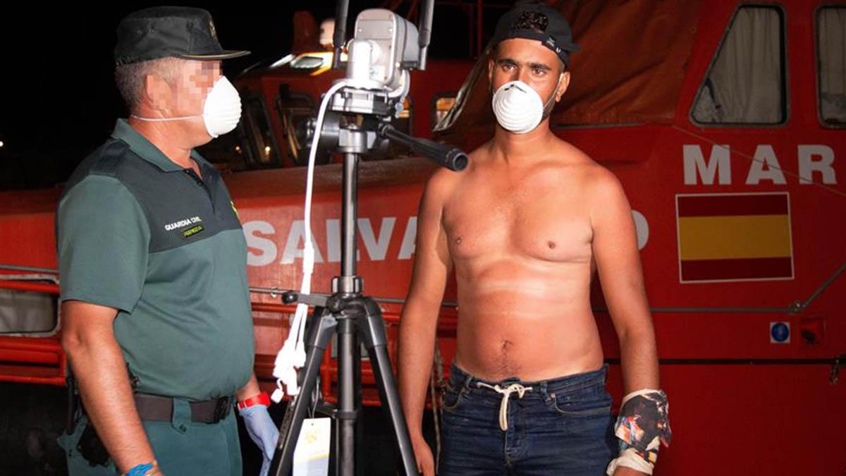 Un guarida civil toma una foto de uno de los cinco inmigrantes de origen magrebí rescatados, a su llegada al puerto de Motril, Granada.