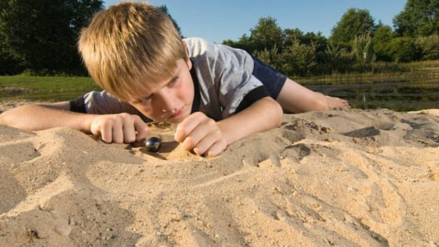 Cómo hacer una pista de canicas para que los niños jueguen en la playa