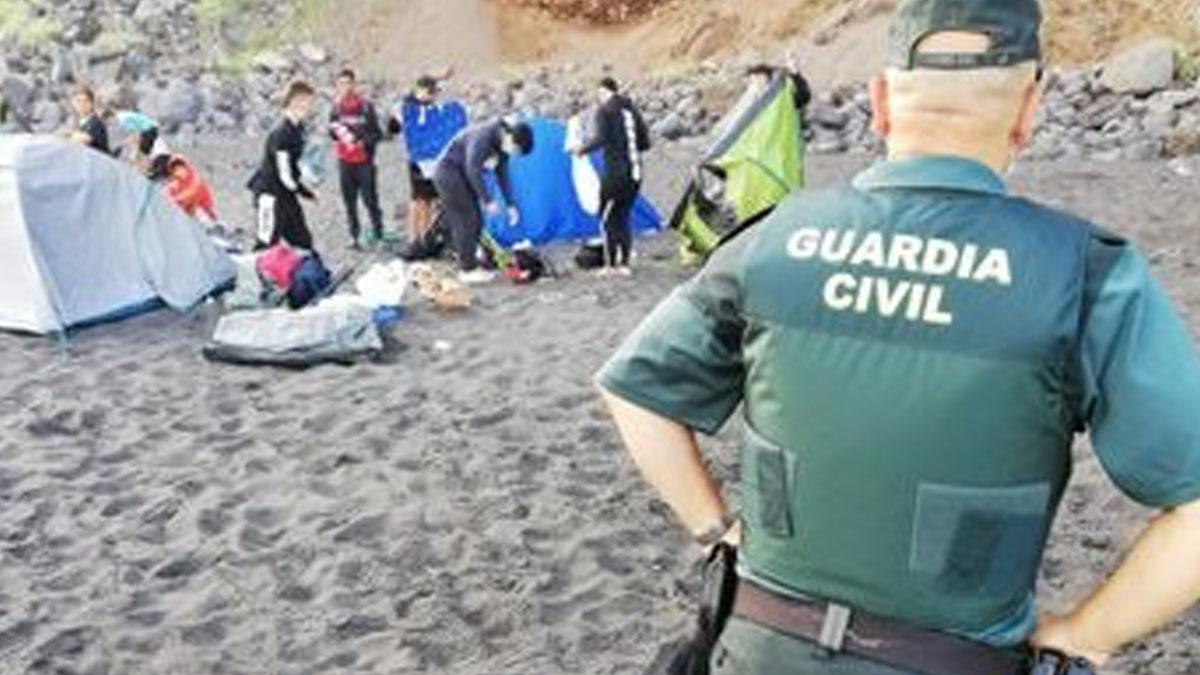 Un agente de la Guardia Civil vigila como los 62 campistas que habían quedado para propagar el coronavirus abandonan la playa de Los Patos en Tenerife. Foto: EP
