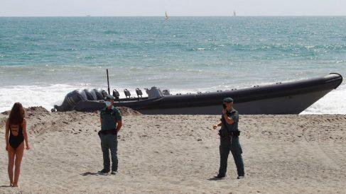 Dos agentes de la Guardia Civil custodian la embarcación incautada a los narcotraficantes.
