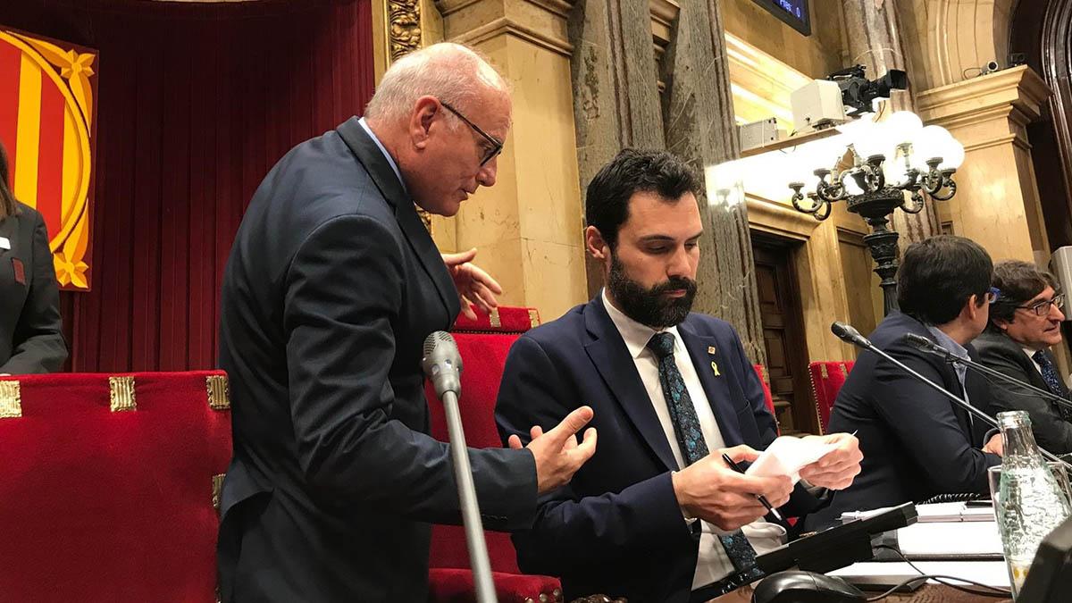 El presidente del Parlament, Roger Torrent, asistido por el secretario general de la Cámara, Xavier Muro.