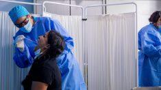 Un trabajador sanitario protegido le realiza a una mujer un test PCR en el Centro de Especialidades Carabanchel Alto