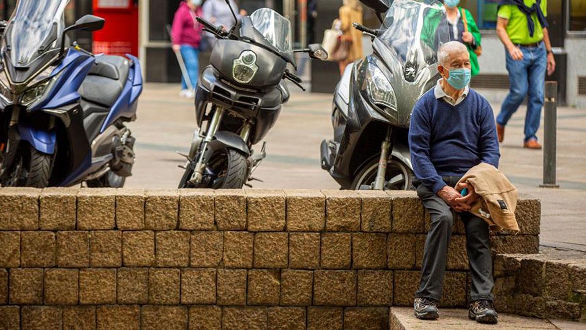 Un hombre espera protegido con mascarilla en la plaza de los Fueros de Vitoria.