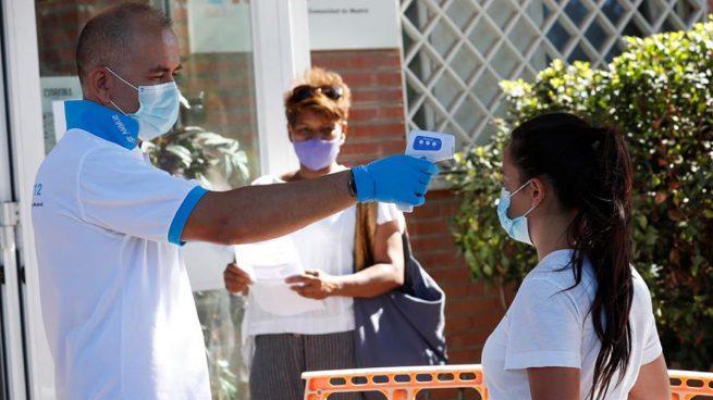 Un paramédico toma la temperatura a una ciudadana antes de acceder al centro de salud Reyes Católicos, de la localidad madrileña San Sebastián de los Reyes, durante la realización de pruebas PCR a vecinos de Alcobendas. Foto: EFE