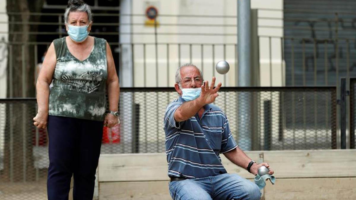 Unos aficionados, protegidos con su mascarilla, juegan a la petanca este domingo en el parque de la Marquesa de L'Hospitalt de Llobregat..