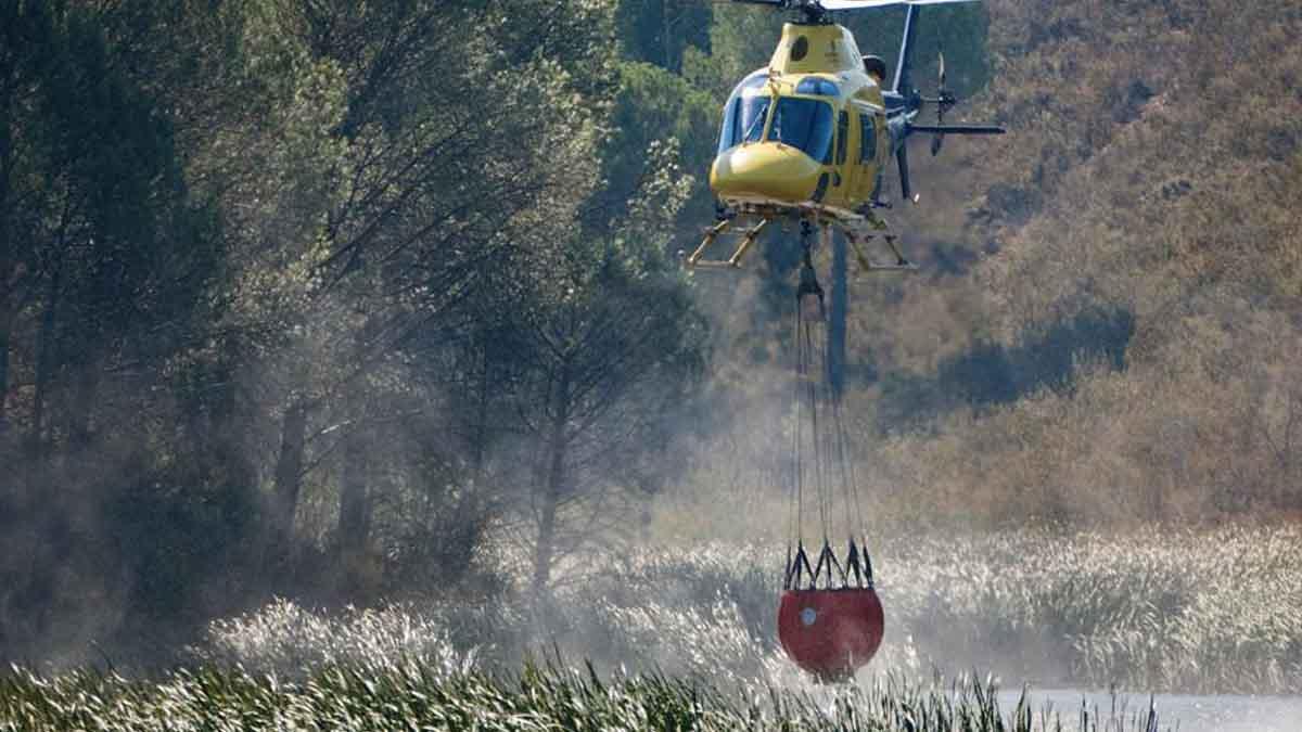 Un helicoptero carga agua para sofocar el avance de las llamas y el fuerte viento en el incendio forestal de Almonaster la Real, en Huelva, que ha obligado a incorporar más medios aéreos. Foto: EFE
