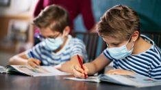Dos niños estudian con las mascarillas puestas