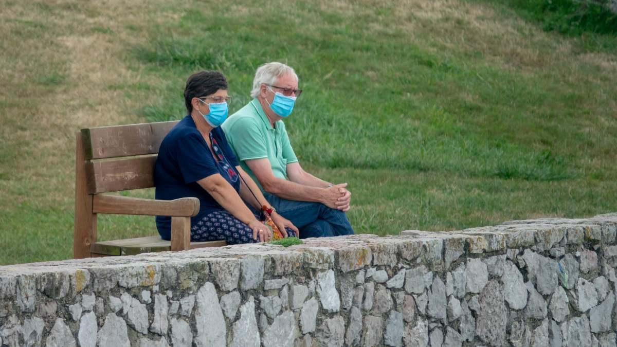 Una pareja sentada con mascarillas en _el banco más bonito del mudo_ en LLanes. Foto: EP