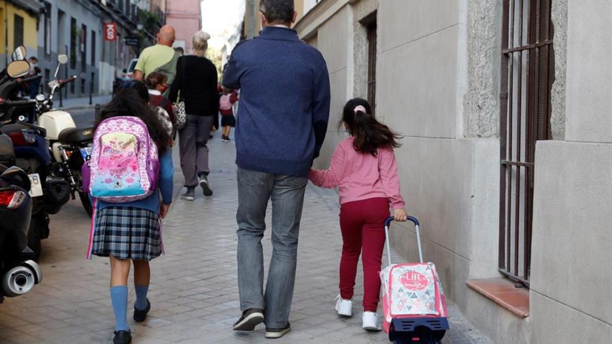 Un padre acompaña a sus hijas en la 'vuelta al cole' en Madrid.
