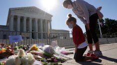 Una madre junto con su hija presentan sus respetos a la juez fallecida Ruth Bader Ginsburg frente al Tribunal Supremo de Estados Unidos. Foto: AFP
