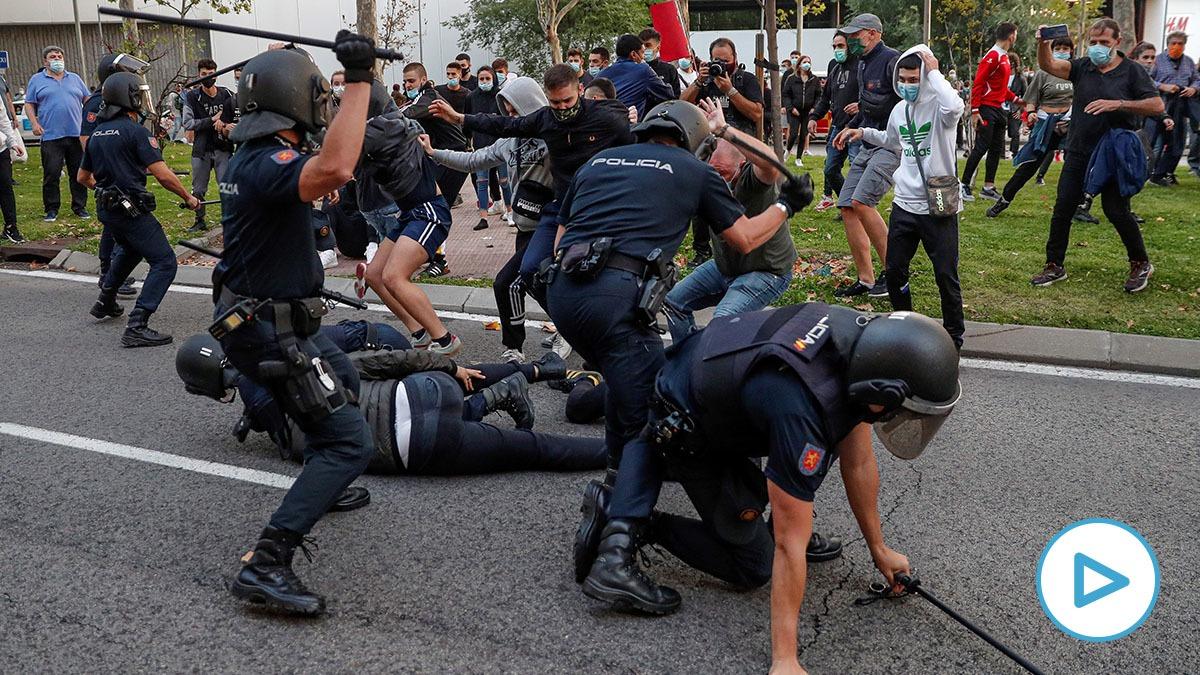 Manifestantes anti Ayuso agrediendo a policías frente a la Asamblea de Madrid. (Foto: Efe)