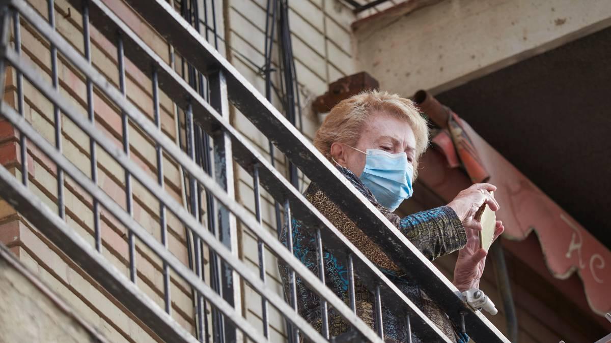Una vecina observa desde su balcón en la localidad de Peralta, en Navarra. Foto. EP