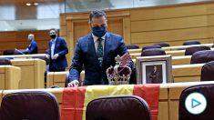Un senador del PP recibe a Pablo Iglesias con una foto de Felipe VI, una corona y una bandera de España.