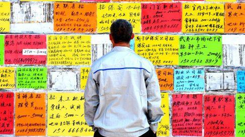 Un transeunte contempla anuncios de trabajo en un mural de la ciudad china de Quingdao.