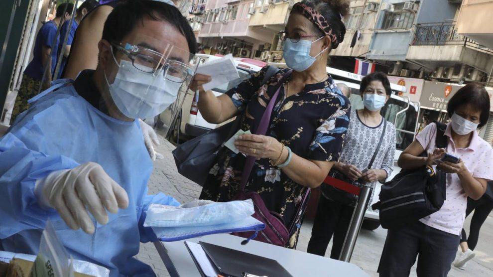 Personal médico de un centro hospitalario de Hong Kong atiende a un grupo de personas que se van a someter a la prueba de coronavirus.