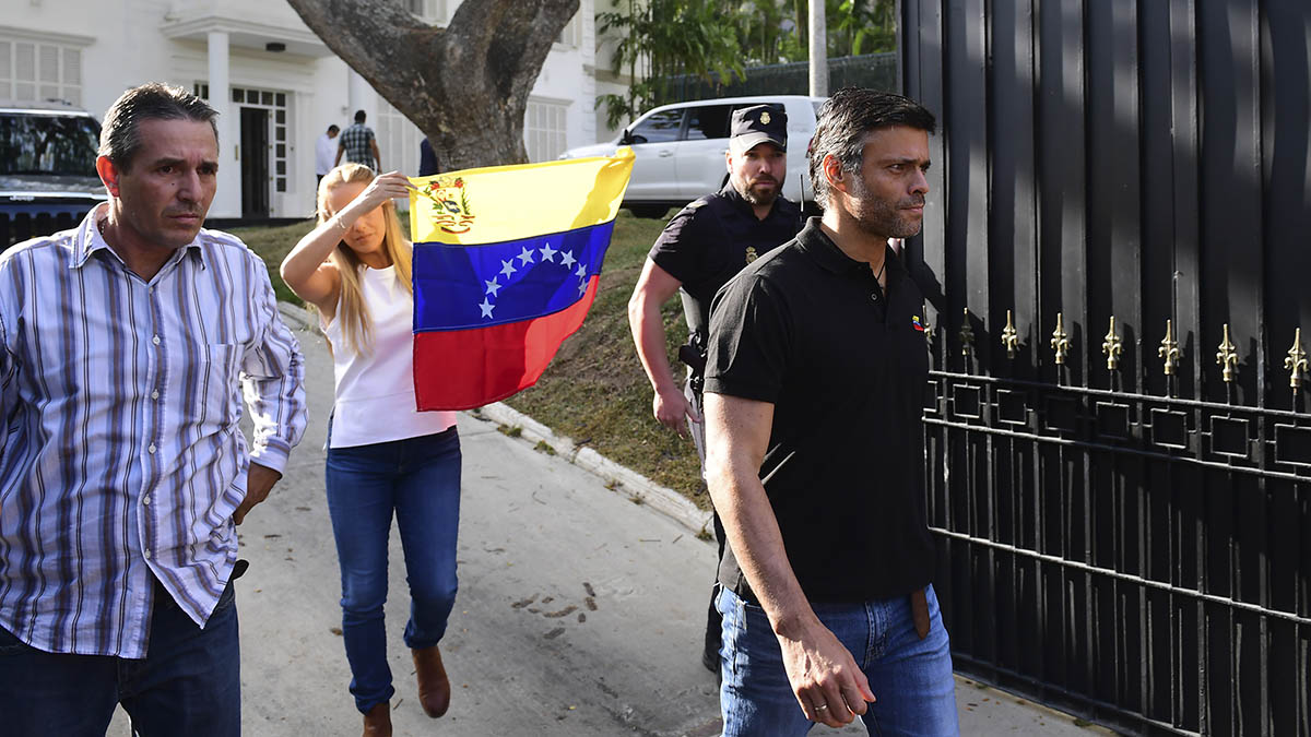 Leopoldo López a las puertas de la embajada española en Caracas. Tras él, su esposa, Lilian Tintoria, blande una bandera venezolana.s