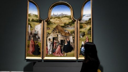 Una persona posa por delante de la obra 'Adoración de los Magos' del Bosco el día de la reapertura de la sala donde permanecen las obras del artista, ubicadas en el Museo del Prado, en Madrid
