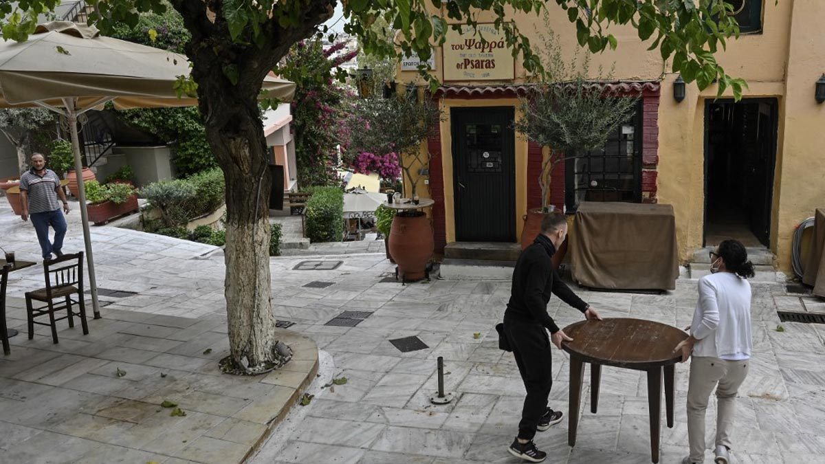 Empleados de una cafetería en un distrito de Atenas, Grecia, recogen la terraza. Foto: AFP