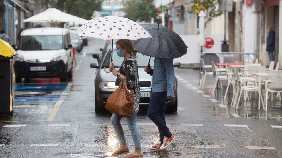 Dos jóvenes pasean bajo la lluvia. Foto: EP