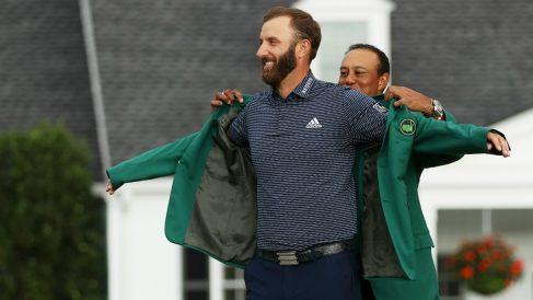 Tiger Woods pone la mítica chaqueta verde a Dustin Johnson. (Getty)