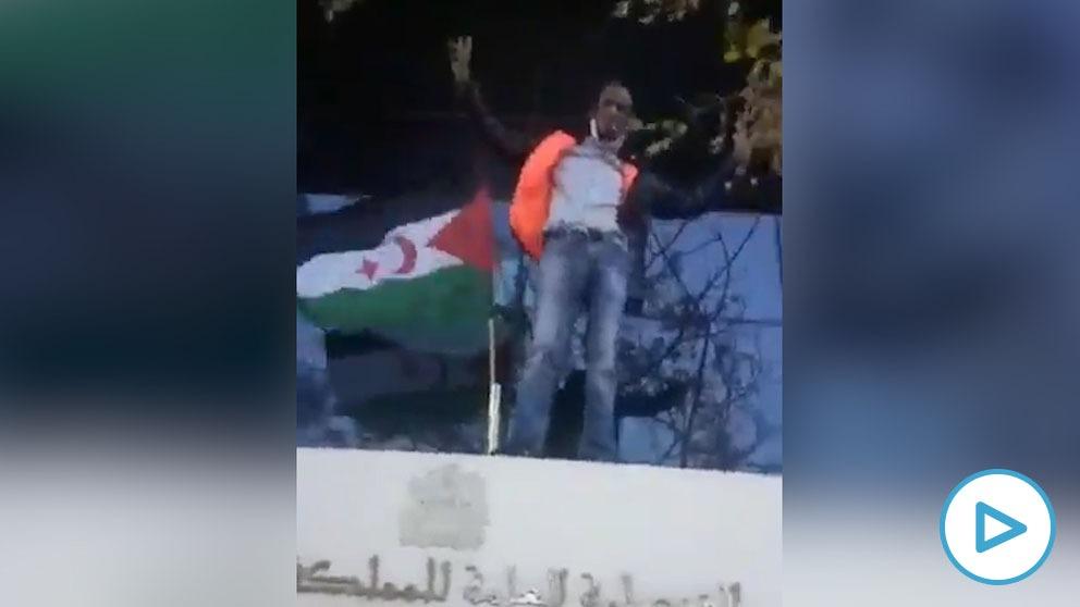 Un activista coloca la bandera saharui en el consulado de Marruecos en Valencia durante una manifestación este domingo.