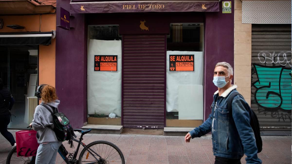 Varias personas caminan delante de un local cerrado por la crisis provocada por el coronavirus. Foto: EP