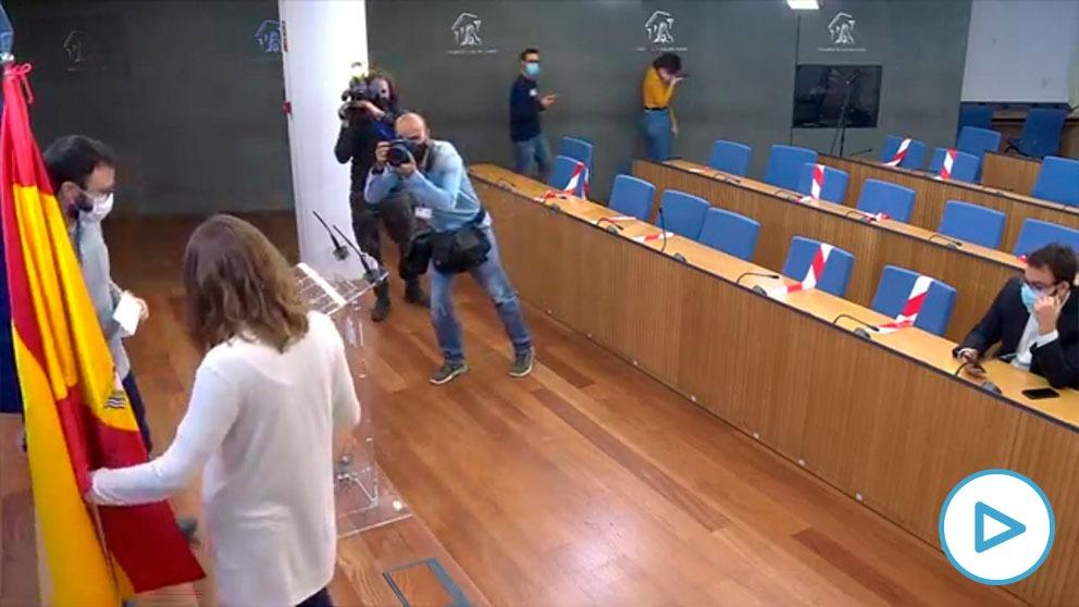 La diputada de la CUP Mireia Vehí apartando la bandera de España en la sala de prensa del Congreso.