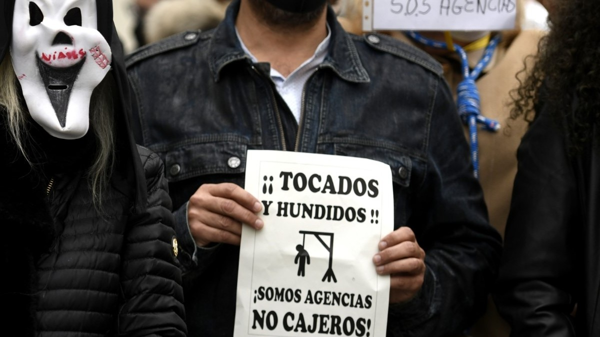 Trabajadores del sector de las agencias se concentran con caretas similares a la del film 'Scary movie' y carteles reivindicativos frente al Congreso de los Diputados, en Madrid (España)