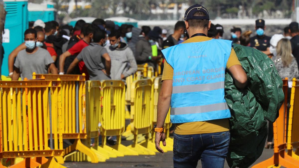 Un agente de la Agencia Europea de Fronteras y Costas FRONTEX, camina junto a varios inmigrantes en el muelle de Arguineguín. (Foto: EFE/ Elvira Urquijo A.)
