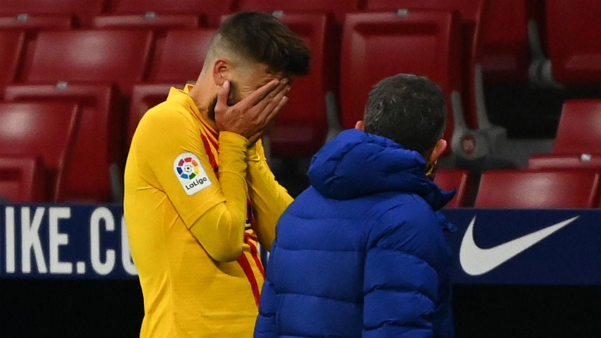 Piqué se lleva las manos a la cara tras lesionarse. (AFP)
