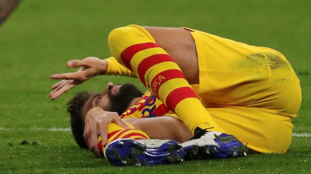 Gerard Piqué, en el césped del Wanda tras sufrir su lesión de ligamentos. (EFE)