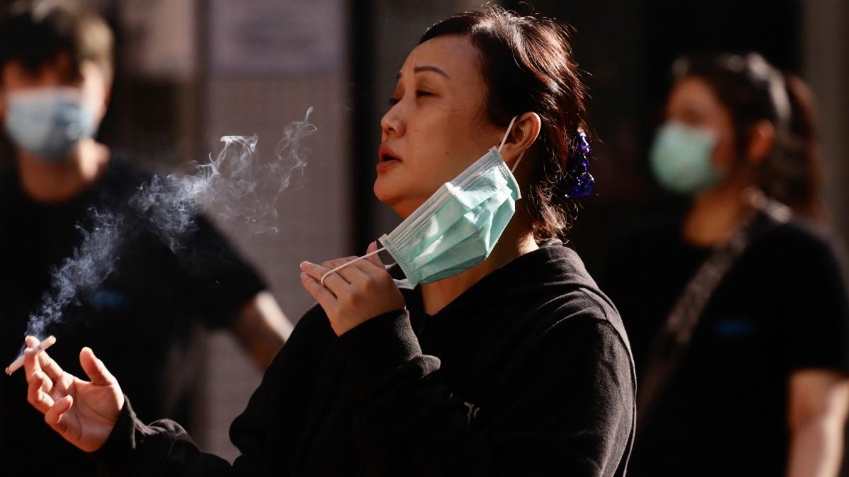 Una mujer se retira la mascarilla para fumar en Hong Kong. (Liau Chung-Ren/ZUMA Wire/dpa)