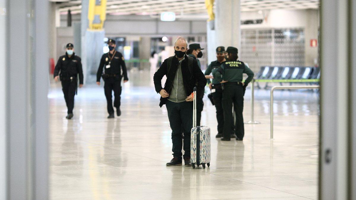 Un pasajero con maleta junto a agentes de la Guardia Civil en la terminal T4. Foto: EP