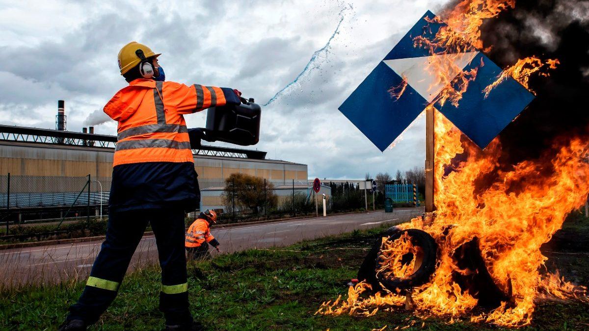 Un trabajador de Alcoa echa gasolina al símbolo corporativo de Alcoa.