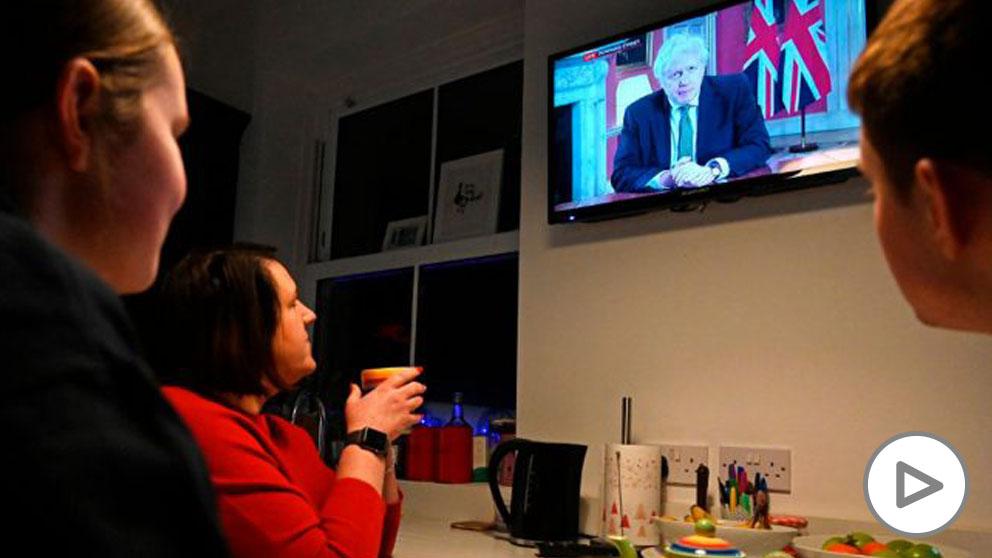 Ciudadanos británicos ven en la televisión el anuncio de un nuevo confinamiento total realizado por el primer ministro Boris Johnson. Foto: AFP