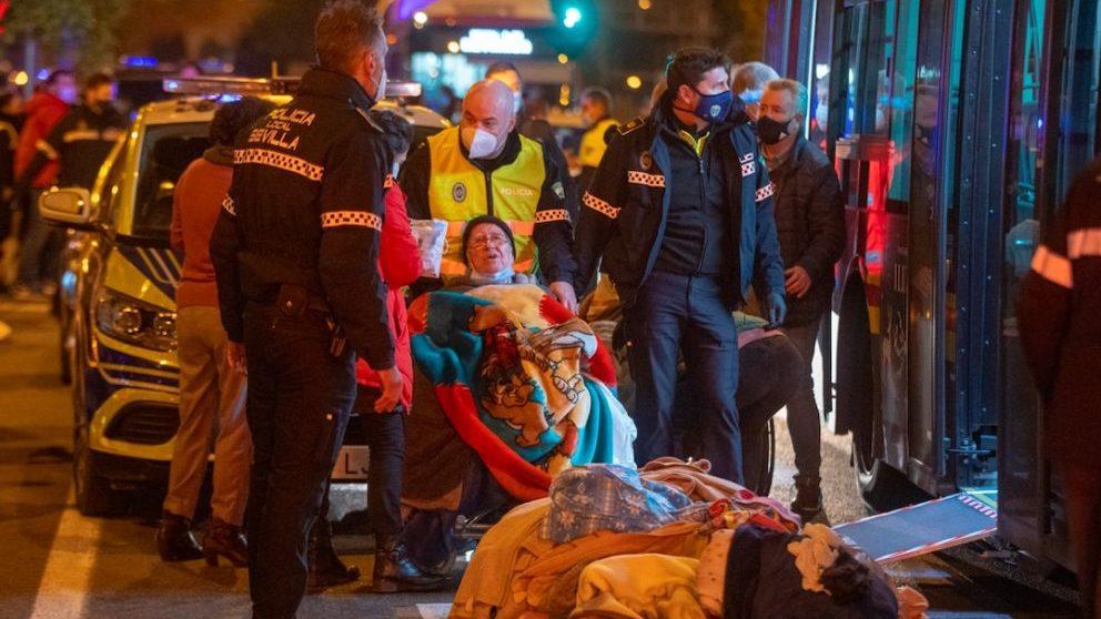 Una anciana es evacuada tras el incendio en una residencia de mayores de Sevilla.