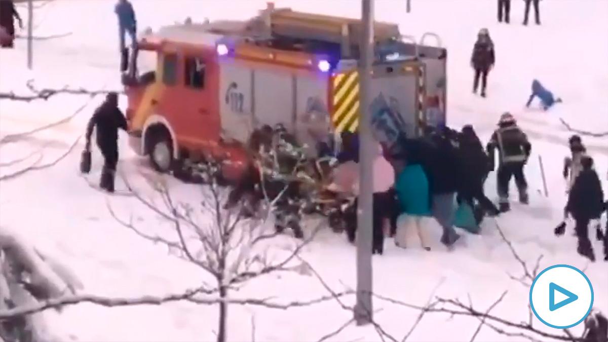 Un grupo de ciudadanos se une para rescatar un camión de bomberos atrapado en la nieve
