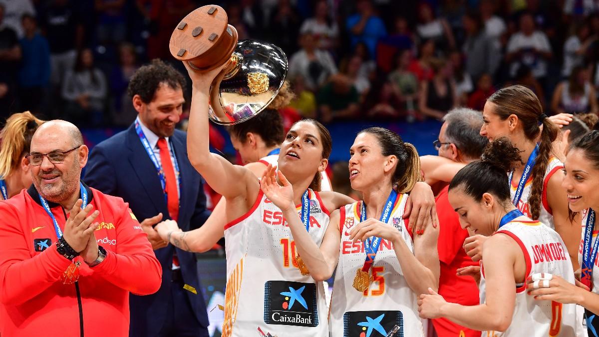 Anna Cruz mira la copa de campeón del EuroBasket que sostiene su amiga Marta Xargay. Lucas Mondelo, seleccionador español, a la izquierda aplaude.