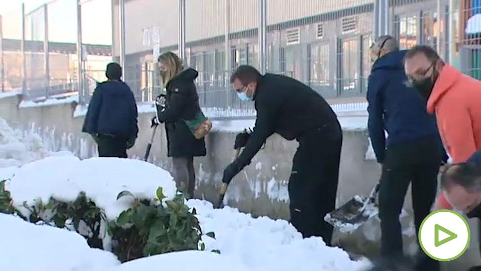 Padres y madres limpian de nieve los accesos a los colegios
