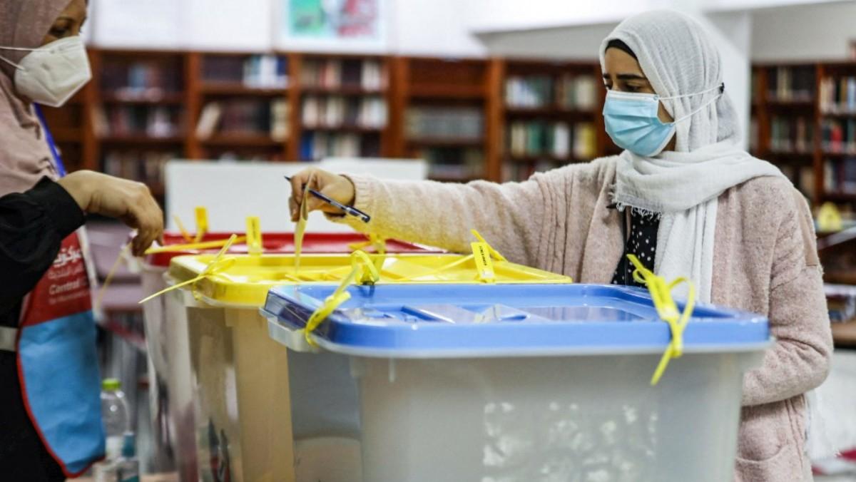 Una mujer libia deposita su voto ataviada con mascarilla y velo. Foto: AFP