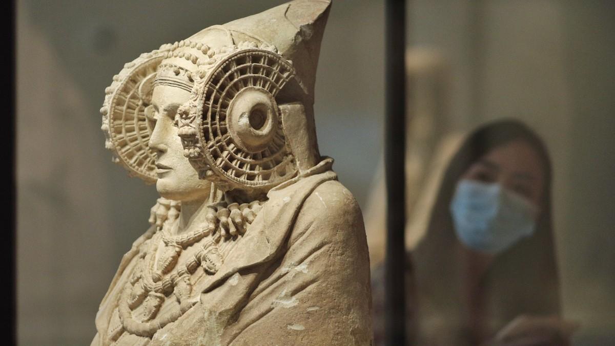 Una persona protegida con mascarilla observa la escultura de La Dama de Elche disponible en el Museo Arqueológico de Madrid. Foto: EP