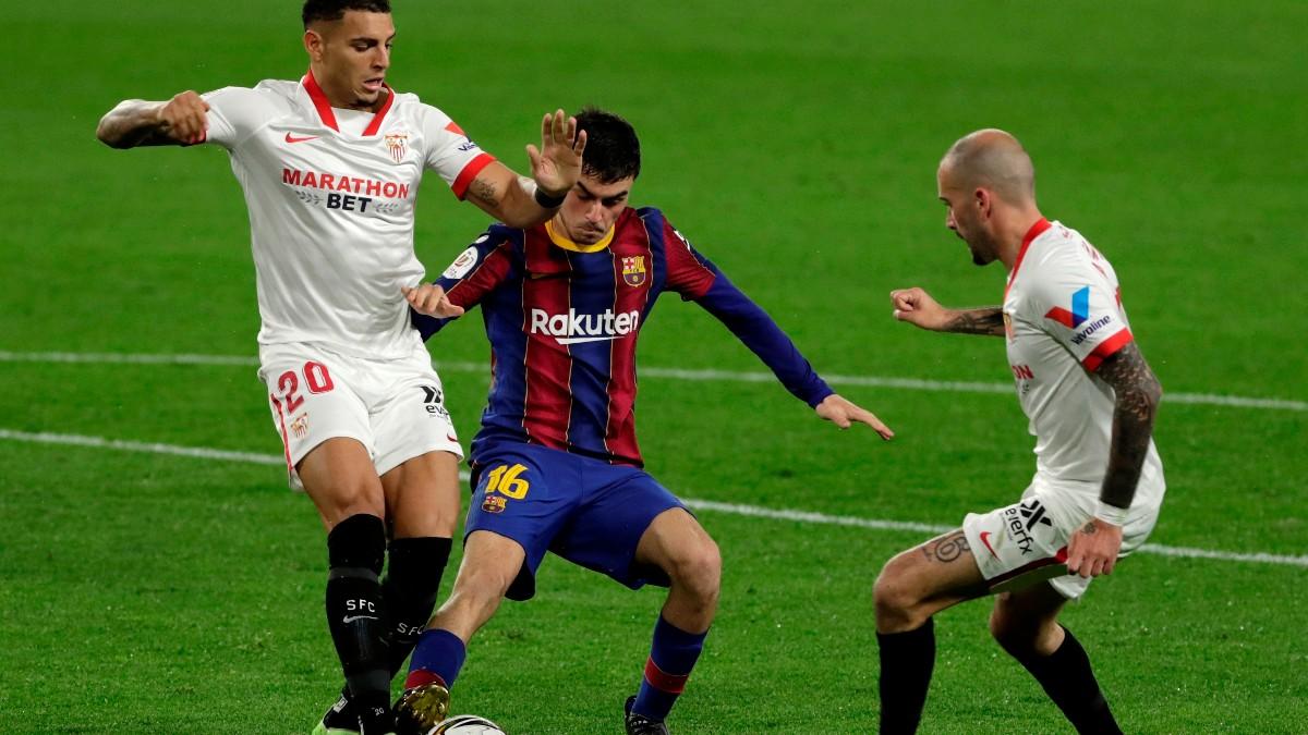 Pedri controla un balón ante Diego Carlos y Aleix Vidal. (EFE)