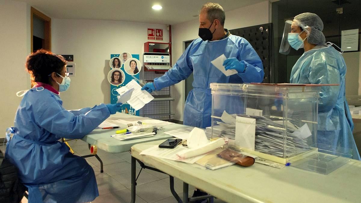 Miembros de una mesa electoral de El Masnou realizan el recuento de votos protegidos con trajes EPI (Foto: EFE).