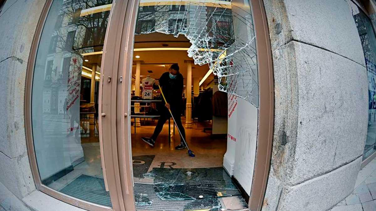 Un dependiente recoge cristales en el interior del establecimiento en la zona de la Puerta de Sol tras los disturbios de la noche del miércoles en una manifestación no autorizada para pedir la libertad del rapero Pablo Hasél. Foto: EFE
